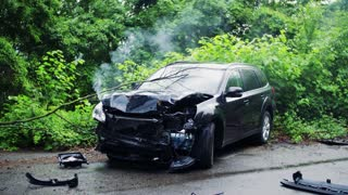 A broken car on the road after an accident, smoke coming out from under the hood.
