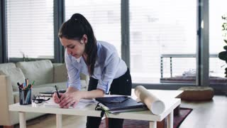 A businesswoman standing at the desk, working. Home office concept. Slow motion.