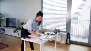 A businesswoman standing at the desk, working. Home office concept.