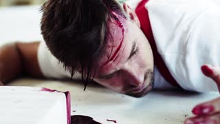 A close-up of a man worker with bleeding wound on head lying on the floor after accident. Working without helmet. Safety at work concept. Close -up.
