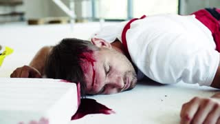 A close-up of a man worker with bleeding wound on head lying on the floor after accident. Working without helmet. Safety at work concept.