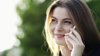 A close-up of a young businesswoman with smartphone outdoors, making a phone call.