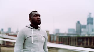 A close up of young sporty black man walking on the bridge in a city. Slow motion.
