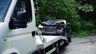 A crashed car being put on a tow truck after an accident. Towing service concept. Slow motion.