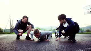 A handsome boy in wheelchair with teenager friends doing push-ups outside. Sport of a disabled man. Slow motion.