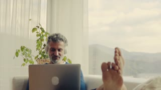 A handsome mature man with laptop and headphone at home, working. Slow motion