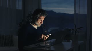 A handsome mature man with laptop computer and smartphone, working in home office at night