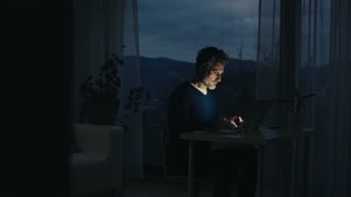 A handsome mature man with laptop computer working in home office at night
