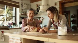 A happy elderly grandmother with an adult granddaughter making dough at home.