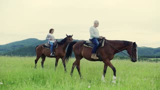 A happy senior couple riding horses on a meadow in nature. Slow motion. Side view.