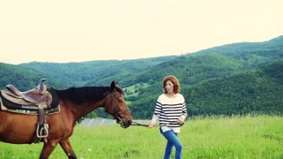 A happy senior woman holding a horse grazing outdoors on a pasture. Slow motion.