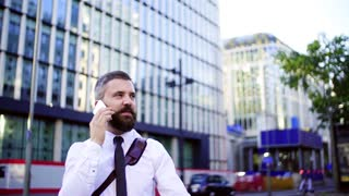 A hipster businessman with smartphone in the city, making a phone call. Slow motion.