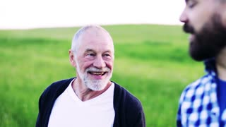 A laughing senior father on a walk with his adult hipster son in nature, talking.