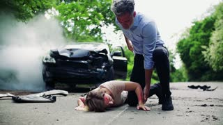 A man helping a young injured woman lying on the road after a car accident, making a phone call. Slow motion.