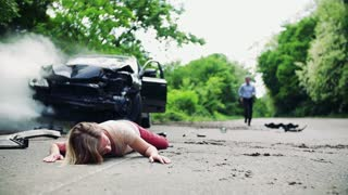 A man running towards a young injured woman lying on the road after a car accident . Slow motion.