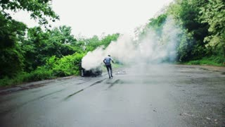A mature man running towards the car in fire after an accident on the countryside road, helping a female driver to get out. Slow motion.