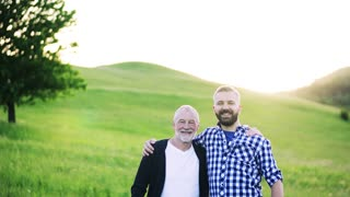 A portrait of a laughing adult hipster son with senior father in nature at sunset, arms around each other. Copy space.