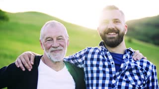 A portrait of a laughing adult hipster son with senior father in nature at sunset, arms around each other.