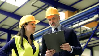 A portrait of an industrial man and woman engineers with clipboard in a factory, talking.