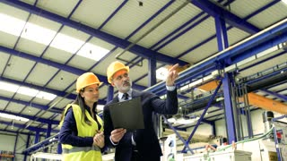 A portrait of an industrial man and woman engineers with clipboard in a factory working.