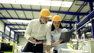 A portrait of an industrial man and woman engineers with clipboard in a factory, working.