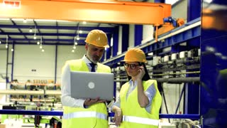 A portrait of an industrial man and woman engineers with laptop in a factory, working.