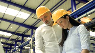 A portrait of an industrial man and woman engineers with laptop in a factory working.