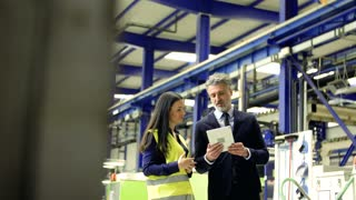 A portrait of an industrial man and woman engineers with tablet in a factory, working.