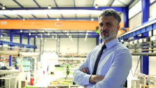 A portrait of an industrial man engineer standing in a factory, arms crossed. Copy space.