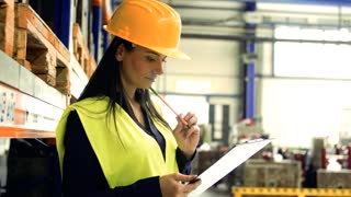 A portrait of an industrial woman engineer in a factory checking documents.