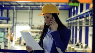 A portrait of an industrial woman engineer in a factory with a smartphone, making a phone call.