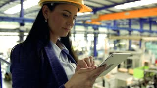 A portrait of an industrial woman engineer in a factory with a tablet, working.