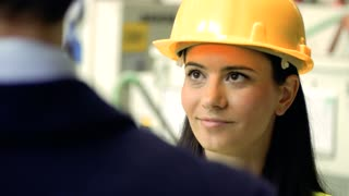 A portrait of an industrial woman engineer standing in a factory, talking to unrecognizable man. Close up.
