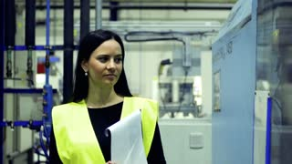 A portrait of an industrial woman engineer walking in a factory, holding documents.