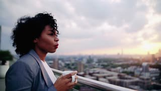 A portrait of black businesswoman standing on a terrace against London rooftop view panorama, drinking coffee. Copy space. Slow motion.