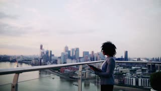 A portrait of black businesswoman standing on a terrace against London rooftop view panorama, making notes. Copy space. Slow motion.