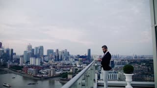 A portrait of businessman using laptop standing against London rooftop view panorama. Copy space. Slow motion.