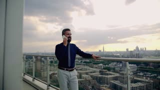 A portrait of businessman with smartphone standing against London rooftop view panorama, making a phone call. Copy space. Slow motion.