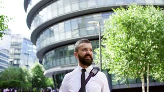 A portrait of hipster businessman with laptop bag standing on the street in London. Slow motion.