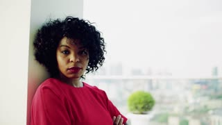 A portrait of serious woman standing by the window against London rooftop view panorama. Copy space. Slow motion.