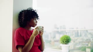 A portrait of woman standing by the window against London rooftop view panorama, drinking coffee. Copy space. Slow motion.