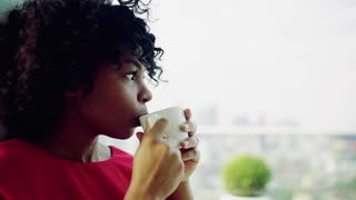 A portrait of woman standing by the window against London rooftop view panorama, holding a cup of coffee. Copy space. Slow motion.