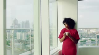 A portrait of woman standing by the window against London rooftop view panorama, holding a cup of coffee. Copy space.