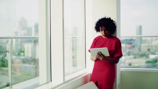 A portrait of woman standing in an office by the window against London rooftop view panorama, using tablet. Copy space. Slow motion.
