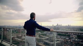 A rear view of businessman standing against London rooftop view panorama, holding railings. Copy space. Slow motion.
