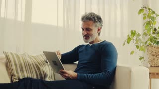 A relaxed handsome mature man using tablet at home. Slow motion