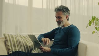 A relaxed handsome mature man using tablet at home
