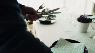 A senior man preparing the table for dinner party at home.