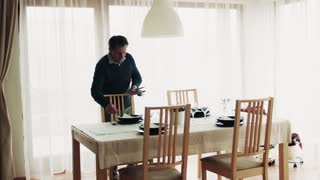 A senior man setting the table for dinner party at home.