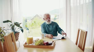 A senior man with a book and coffee sitting at the table inside, reading a book. Slow motion.